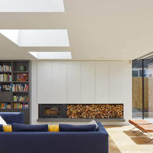 Photo of a medium sized contemporary living room in London with white walls, light hardwood flooring, beige floors, a metal fireplace surround and a wood burning stove.