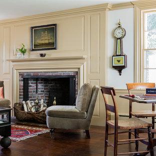 Foto di un soggiorno chic chiuso con sala giochi, pareti gialle, camino classico, cornice del camino in mattoni e nessuna TV