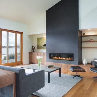 Inredning av ett modernt allrum med öppen planlösning, med vita väggar, ljust trägolv, en bred öppen spis och beiget golv
