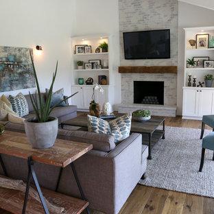 Immagine di un soggiorno country con pareti bianche, pavimento in legno massello medio, camino classico, cornice del camino in mattoni e TV a parete
