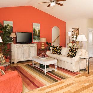 Foto de salón abierto, clásico, sin chimenea, con parades naranjas y suelo de madera clara