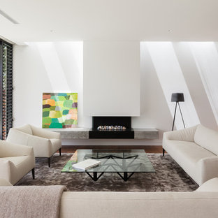 Foto di un soggiorno moderno di medie dimensioni e aperto con pareti bianche, pavimento in legno massello medio, cornice del camino in intonaco, sala formale e camino lineare Ribbon