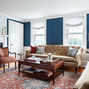 Example of a classic formal medium tone wood floor and brown floor living room design in Boston with blue walls and a standard fireplace