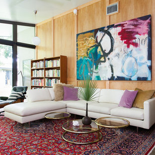 Example of a 1950s linoleum floor living room library design in Austin with brown walls and no tv