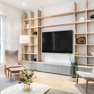 Photo of a medium sized scandinavian enclosed living room in London with white walls, light hardwood flooring, no fireplace, a wall mounted tv and brown floors.