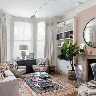 ロンドンのトランジショナルスタイルのおしゃれなLDK (ピンクの壁、無垢フローリング、標準型暖炉、埋込式メディアウォール、茶色い床) の写真