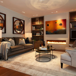 Medium sized traditional living room in London with grey walls, a ribbon fireplace, a wall mounted tv, brown floors and medium hardwood flooring.