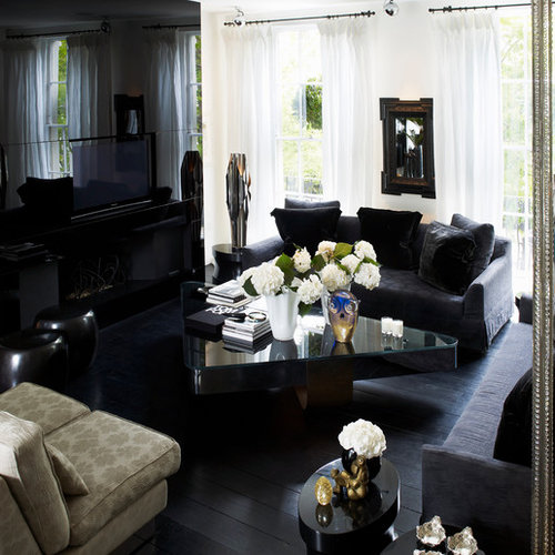 Example Of A Large Trendy Black Floor Living Room Design In London With Wall