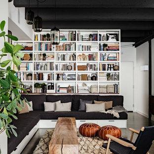 Cette image montre un salon avec une bibliothèque ou un coin lecture urbain avec béton au sol.