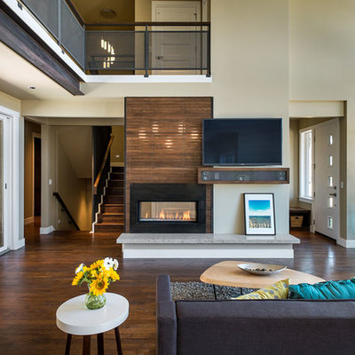 Inspiration for a large contemporary open concept medium tone wood floor living room remodel in Portland with beige walls, a two-sided fireplace and a wall-mounted tv