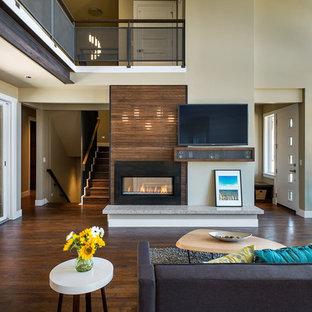 Foto de salón abierto, contemporáneo, grande, con paredes beige, chimenea de doble cara, televisor colgado en la pared y suelo de madera en tonos medios
