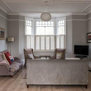 Imagen de biblioteca en casa abierta, bohemia, grande, con paredes grises, suelo de madera clara, chimenea tradicional, marco de chimenea de piedra y televisor independiente