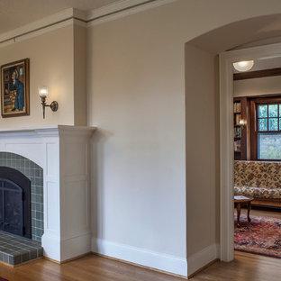 Idee per un grande soggiorno american style aperto con sala formale, pareti beige, parquet chiaro, camino classico e cornice del camino piastrellata