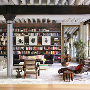 Example of a large trendy light wood floor living room library design in New York with no fireplace and no tv