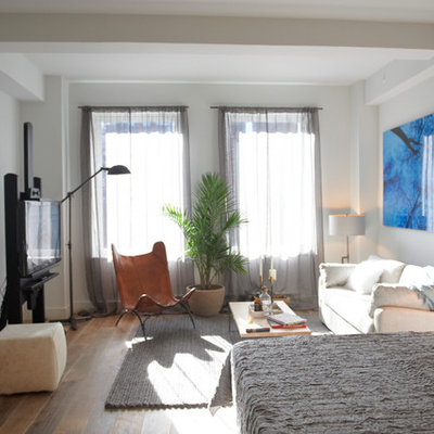 Example of a mid-sized trendy formal and open concept medium tone wood floor living room design in New York with white walls