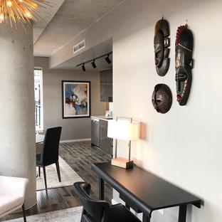 Idee per un piccolo soggiorno design aperto con pareti grigie, pavimento in laminato, nessun camino, nessuna TV e pavimento marrone
