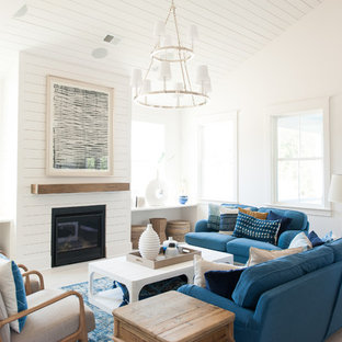 Inspiration for a beach style medium tone wood floor and brown floor living room remodel in Charleston with white walls and a standard fireplace