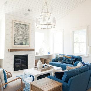 チャールストンのビーチスタイルのおしゃれなリビング (白い壁、無垢フローリング、標準型暖炉、茶色い床) の写真