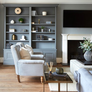 Inspiration for a traditional living room in London with a reading nook, grey walls, medium hardwood flooring, a standard fireplace, a wall mounted tv and brown floors.