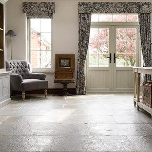 Idee per un soggiorno country di medie dimensioni e chiuso con sala formale, pareti bianche, pavimento in pietra calcarea, stufa a legna, cornice del camino in mattoni e pavimento grigio