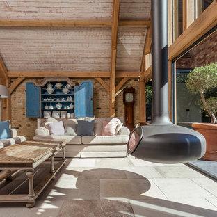 Immagine di un soggiorno country aperto con camino sospeso e pavimento grigio