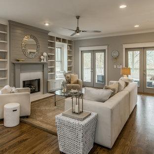 Ejemplo de salón para visitas abierto, tradicional renovado, de tamaño medio, sin televisor, con paredes grises, suelo de madera en tonos medios y chimenea tradicional