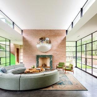 ヒューストンのミッドセンチュリースタイルのおしゃれなLDK (赤い壁、コンクリートの床、標準型暖炉、グレーの床) の写真
