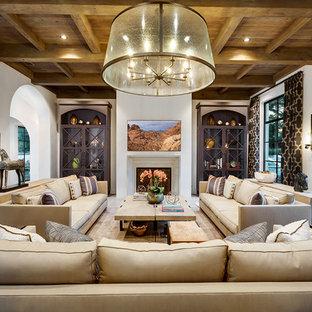Geräumiges, Offenes Mediterranes Wohnzimmer mit weißer Wandfarbe, Kalkstein und Wand-TV in Sonstige
