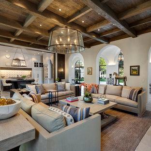Cette image montre un très grand salon méditerranéen ouvert avec un mur blanc, un sol en calcaire et un sol gris.