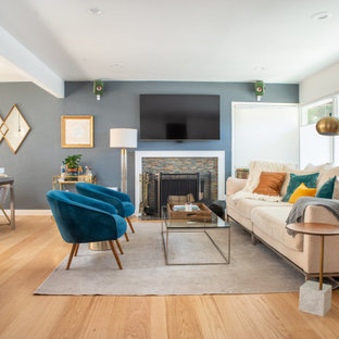 This is an example of a transitional open concept living room in San Francisco with blue walls, medium hardwood floors, a standard fireplace, a wall-mounted tv and brown floor.