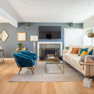 Cette image montre un salon traditionnel ouvert avec un mur bleu, un sol en bois brun, une cheminée standard, un manteau de cheminée en pierre de parement, un téléviseur fixé au mur et un sol marron.