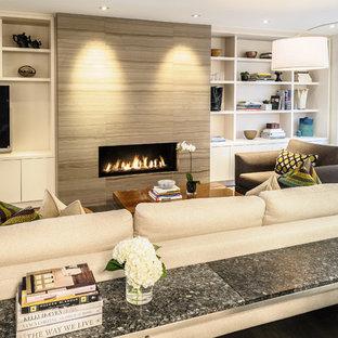 Imagen de salón abierto, contemporáneo, de tamaño medio, con paredes blancas, suelo de madera clara, chimenea lineal, marco de chimenea de piedra y pared multimedia