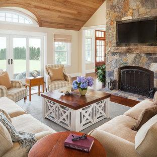 Inredning av ett klassiskt vardagsrum, med beige väggar, en standard öppen spis och en spiselkrans i sten