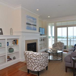 ボストンの中サイズのビーチスタイルのおしゃれなLDK (フォーマル、ベージュの壁、濃色無垢フローリング、標準型暖炉、石材の暖炉まわり、据え置き型テレビ) の写真
