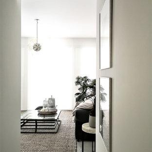 Ejemplo de biblioteca en casa abierta, bohemia, de tamaño medio, sin chimenea, con paredes blancas, suelo de baldosas de cerámica y suelo blanco