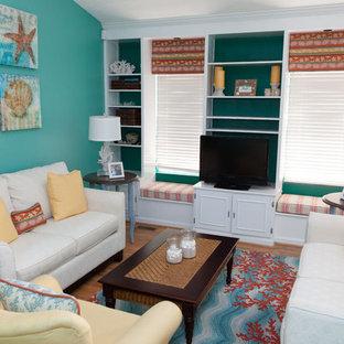 ワシントンD.C.の中サイズのトロピカルスタイルのおしゃれなリビング (青い壁、据え置き型テレビ、無垢フローリング、暖炉なし、茶色い床) の写真