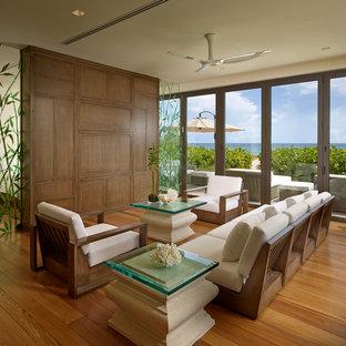 Foto di un piccolo soggiorno etnico aperto con pareti beige, parquet chiaro e parete attrezzata