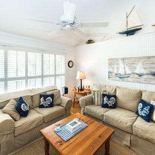チャールストンの大きいビーチスタイルのおしゃれなLDK (白い壁、無垢フローリング、標準型暖炉、木材の暖炉まわり、据え置き型テレビ) の写真