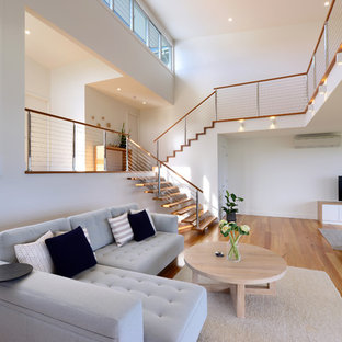 Large contemporary open concept living room in Wollongong with white walls, medium hardwood floors, a freestanding tv and brown floor.