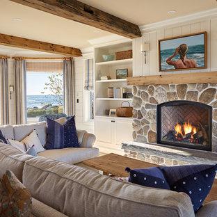 Modelo de biblioteca en casa costera, sin televisor, con paredes blancas, chimenea tradicional y marco de chimenea de piedra