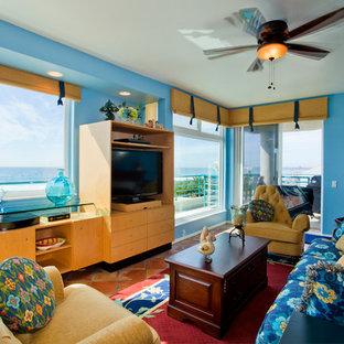 Idee per un soggiorno tropicale di medie dimensioni e aperto con pareti blu, pavimento in terracotta, camino classico, cornice del camino in legno e parete attrezzata