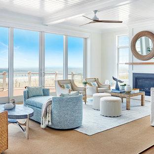 ニューヨークの巨大なビーチスタイルのおしゃれなLDK (白い壁、淡色無垢フローリング、テレビなし、フォーマル、標準型暖炉、ベージュの床) の写真