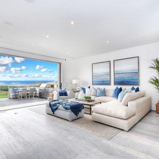 オレンジカウンティの大きいビーチスタイルのおしゃれなLDK (白い壁、淡色無垢フローリング、標準型暖炉、壁掛け型テレビ、グレーの床、石材の暖炉まわり) の写真