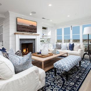 オレンジカウンティの大きいビーチスタイルのおしゃれなLDK (白い壁、濃色無垢フローリング、標準型暖炉、石材の暖炉まわり、壁掛け型テレビ) の写真