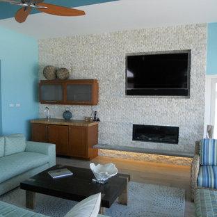 ニューヨークの大きいビーチスタイルのおしゃれなリビング (青い壁、淡色無垢フローリング、横長型暖炉、石材の暖炉まわり、グレーの床) の写真
