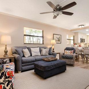 マイアミの中サイズのビーチスタイルのおしゃれなLDK (グレーの壁、ラミネートの床、暖炉なし、壁掛け型テレビ、ベージュの床) の写真