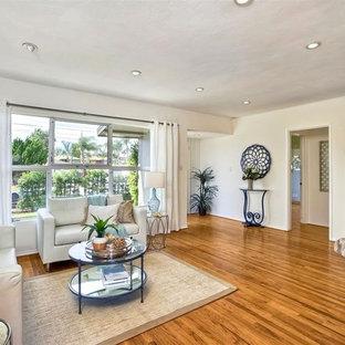 サンディエゴの中サイズのビーチスタイルのおしゃれなLDK (白い壁、無垢フローリング、暖炉なし、据え置き型テレビ、茶色い床) の写真