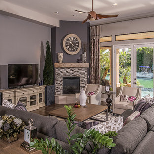 Foto di un soggiorno classico di medie dimensioni e aperto con pareti viola, pavimento in legno massello medio, camino ad angolo, cornice del camino piastrellata e TV autoportante