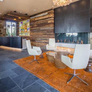 Foto de salón abierto, ecléctico, grande, sin televisor, con paredes marrones, suelo de pizarra, chimenea lineal, marco de chimenea de piedra y suelo gris