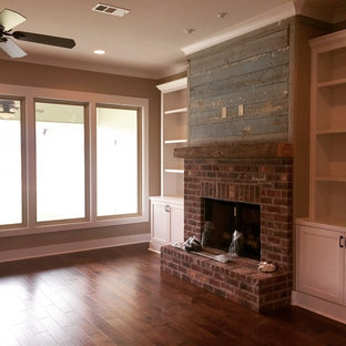 Example of a mid-sized mountain style open concept dark wood floor living room design in New Orleans with a standard fireplace, a brick fireplace and brown walls